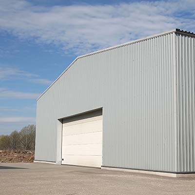 Gray warehouse commercial building without gutters.