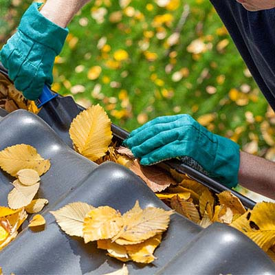 Depiction demonstrating our cleaning services by a person cleaning out clogged leaves from a seamless rain gutter.
